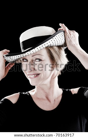 Woman with hat performing on stage, black background - stock photo