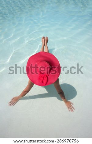 Woman with hat relaxing in a blue pool - stock photo