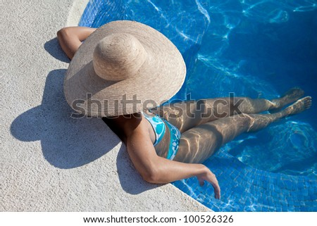 Woman with hat sitting in the pool enjoying her vacation. - stock photo
