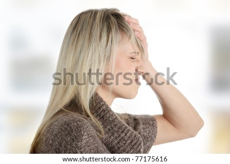 Woman with headache holding her hand to the head - stock photo