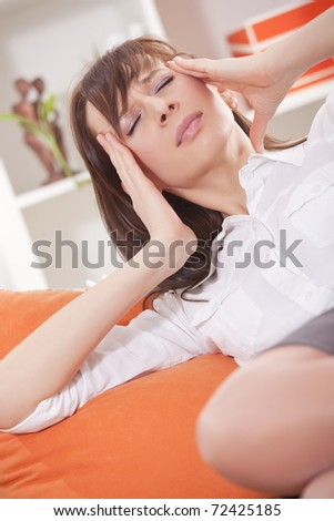 woman with headache holding her head with both hands - stock photo