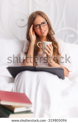 Woman with headache studying in the bed