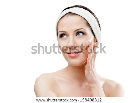 Woman with headband making face moistening procedures, isolated - stock photo