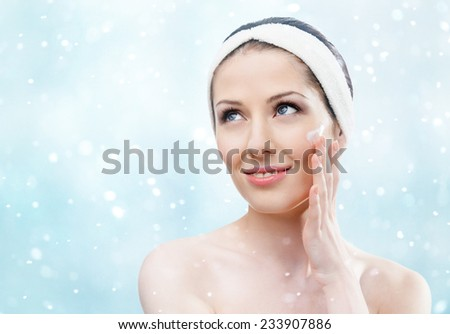 Woman with headband making face moistening procedures, winter background - stock photo