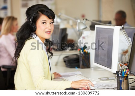 Woman With Headset Working At Desk In Busy Creative Office - stock photo