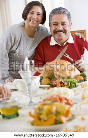 Woman With Her Arm Around Her Husband,Who Is Getting Ready To Carve A Turkey - stock photo
