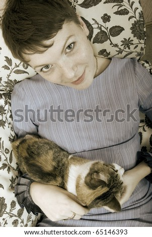 woman with her cat in her apartment - stock photo