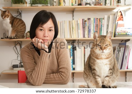 Woman with her cats in home, focus on the woman. - stock photo