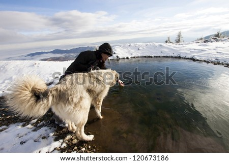 Woman with her dog in snowy mountain scenery - stock photo