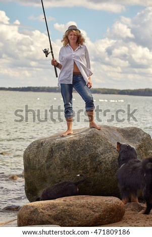 woman with her dogs on sea beach standing