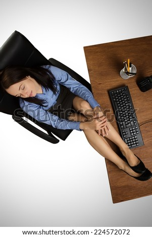 woman with her feet up on her desk at work relaxing, taken from a birds eye view - stock photo