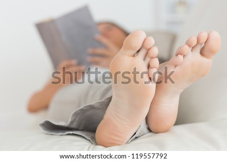 Woman with her feet up reading a book on the sofa - stock photo