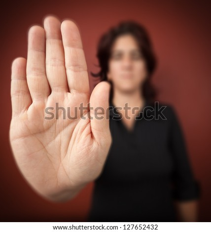 Woman with her hand extended signaling to stop (only her hand is in focus) on a red background