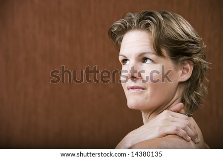 Woman with her hand on her shoulder looking left - stock photo