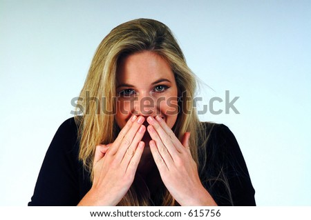 Woman with her hands over her mouth. - stock photo