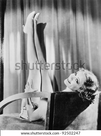 Woman with her legs in the air sitting on a chair looking over the backrest - stock photo