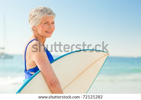 Woman with her surfboard at the beach - stock photo