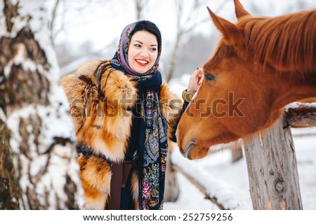 Woman with here horse in winter park