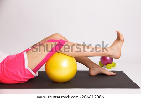 Woman with injured knee doing physiotherapy exercise - stock photo