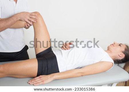 woman with injured knee making physiotherapy - stock photo