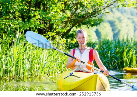 woman with kayak or canoe on forest river - stock photo