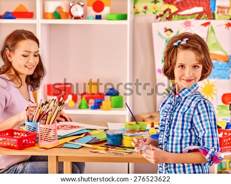 Woman  with kid painting  in school. Education. - stock photo