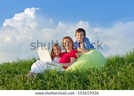 Woman with kids hanging out relaxing outdoors - stock photo
