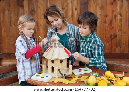 Woman with kids in autumn painting the bird house - preparing it for winter time - stock photo