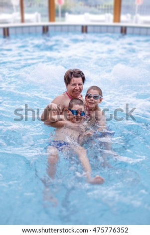 Woman with kids in the swimming pool