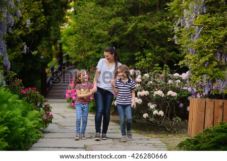 Woman with kids to spend time in the park. Mom keeps children's hands. All animated conversation. Family walking along  surrounded by flowering plants. Time spent in nature for better child health
