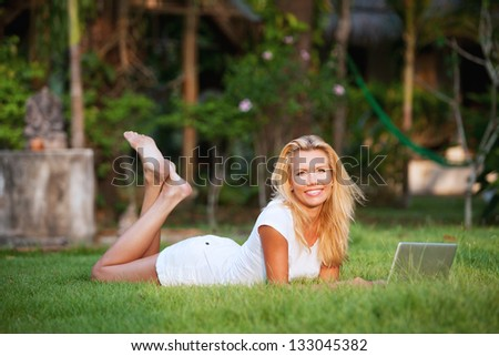 woman with laptop on the grass - stock photo