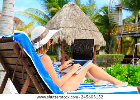 woman with laptop on tropical beach vacation - stock photo