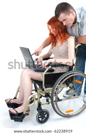woman with laptop on wheelchair, with man showing her something - stock photo