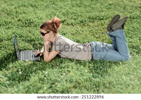 Woman with laptop relaxing in park - stock photo