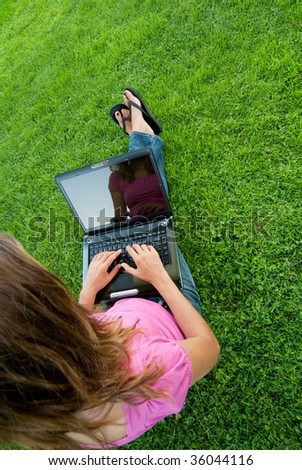 Woman with laptop sit relaxed green grass - stock photo