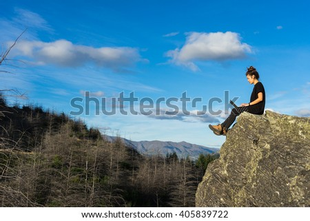 Woman with laptop sitting on the mountain - stock photo