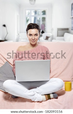 woman with laptop sitting on the sofa. At home - stock photo