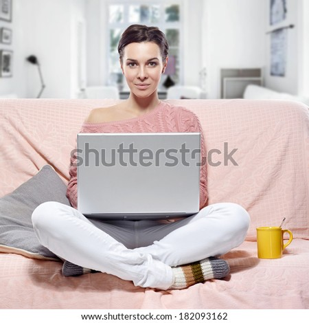 woman with laptop sitting on the sofa. At home