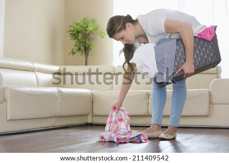 Woman with laundry basket picking clothes from floor in living room - stock photo