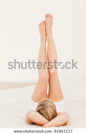 Woman with legs up in her bedroom - stock photo