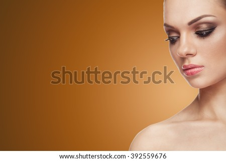 Woman with light make up on brown background with copy space available in studio photo - stock photo