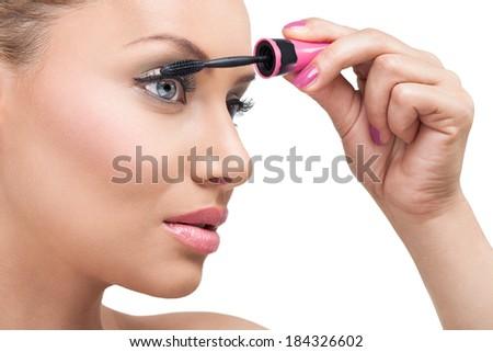Woman  with long eyelashes and mascara brush - stock photo