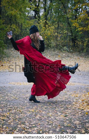 woman with long flowing hair in a burgundy red plum dress in autumn forest