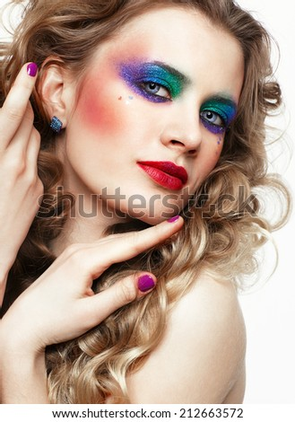 Woman with long golden curly hairs and bright festive eyes make-up