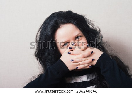 Woman with long hair covering her face with her hands. Gray background - stock photo