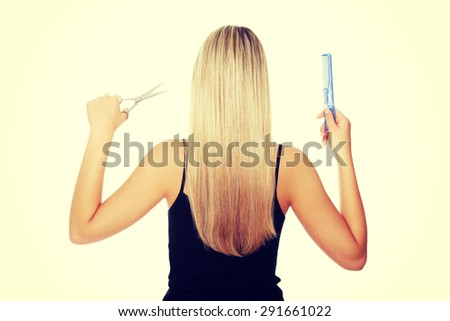 Woman with long hair holding comb and scissors - stock photo