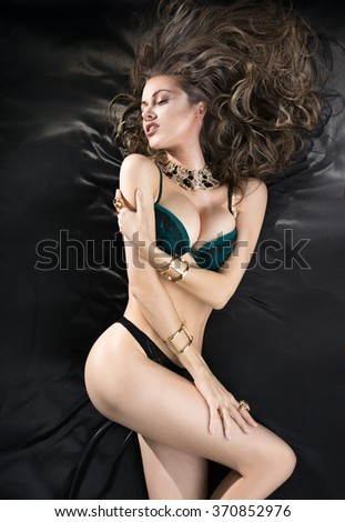 Woman with long hair in lingerie lying on a black silk sheets - stock photo