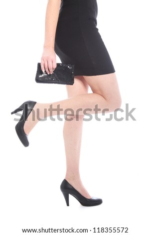 Woman with long legs and black heels holding a small black purse isolated on white - stock photo