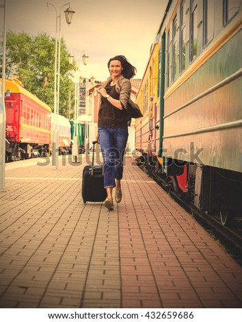 woman with luggage on the station platform runs  for passenger train along the railcar. instagram image filter retro style - stock photo