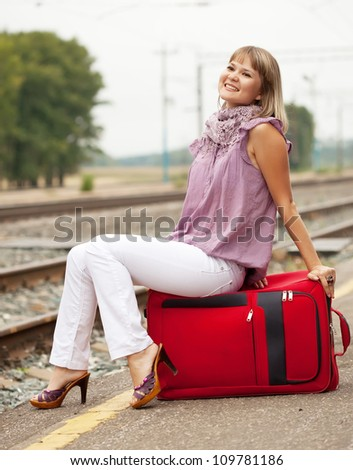 woman with luggage waiting  train on  railroad - stock photo
